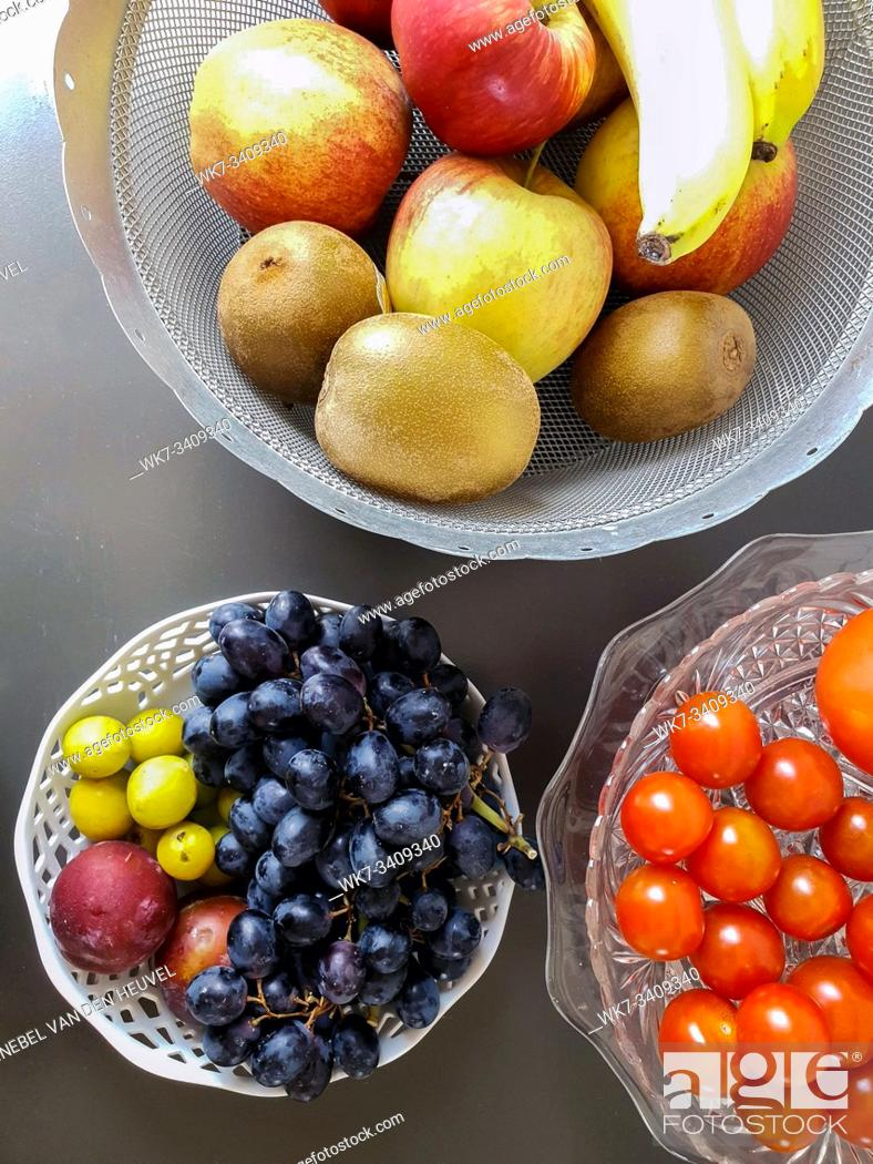 Stock Photo: Healthy and fresh various fruit in a bowl on the table top view, grapes, apples, bananas healthy lifestyle colorful.