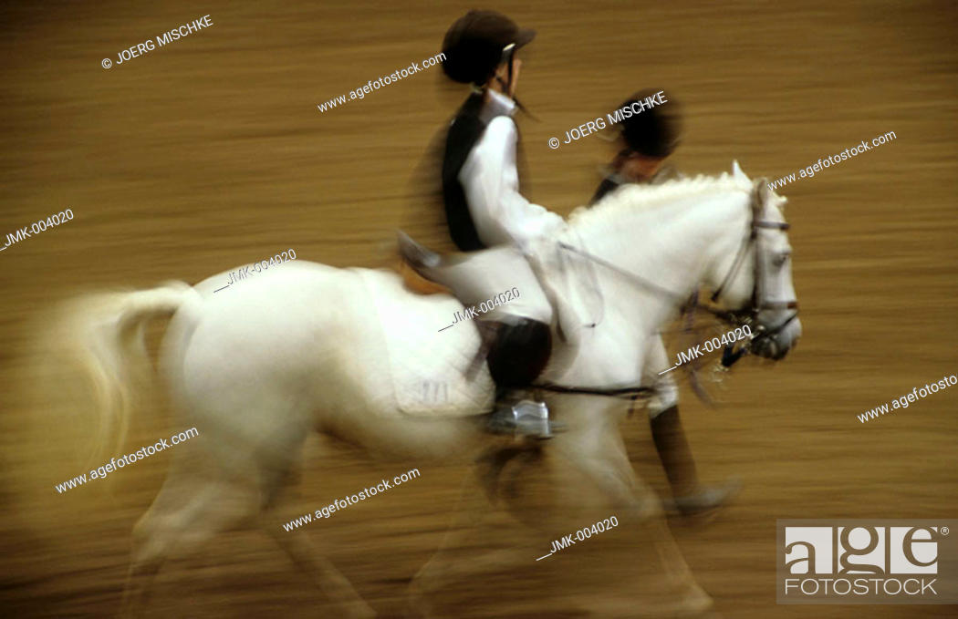 Stock Photo: A little child, 5-10 years old, riding a horse at a horse show, the horse is leaded by an adult, blurred.
