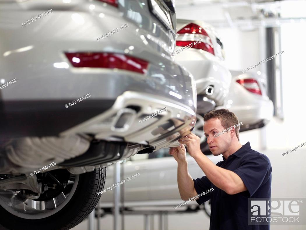 Stock Photo: Mechanic working on car in auto repair shop.