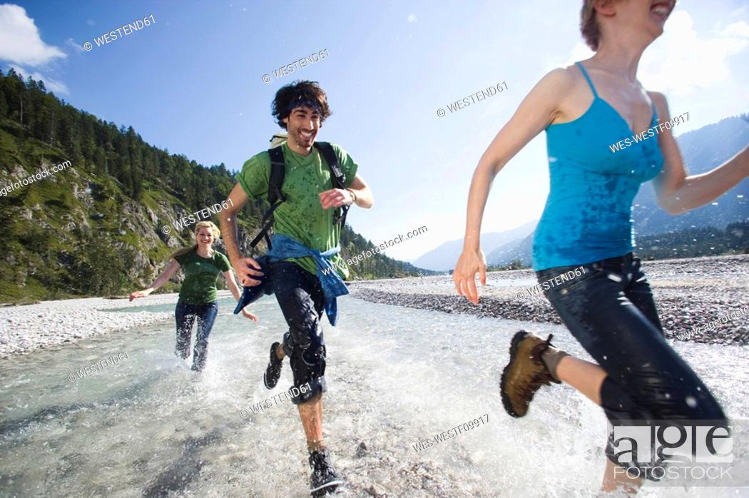Stock Photo: Germany, Bavaria, Tölzer Land, Young people running through river.