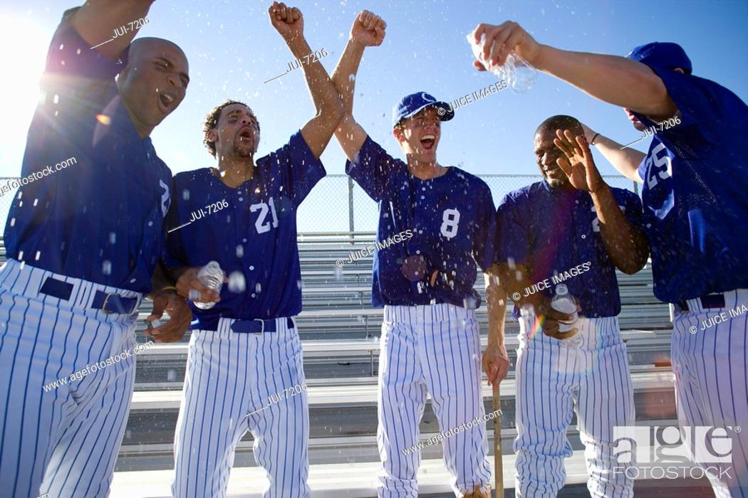 Stock Photo: Baseball team, in blue uniform, punching air in victory post match, cheering lens flare.