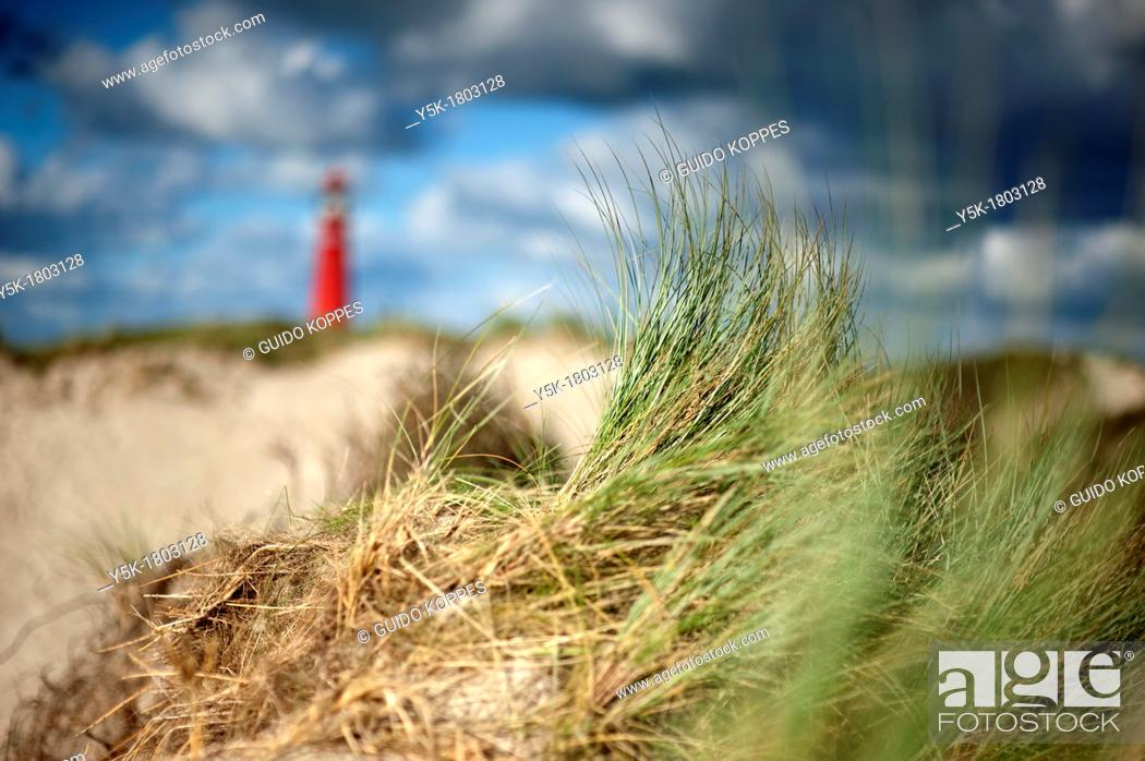 Stock Photo: Schiermonnikoog, Netherlands. Lighthouse in sand-dunes under a stormy sky.