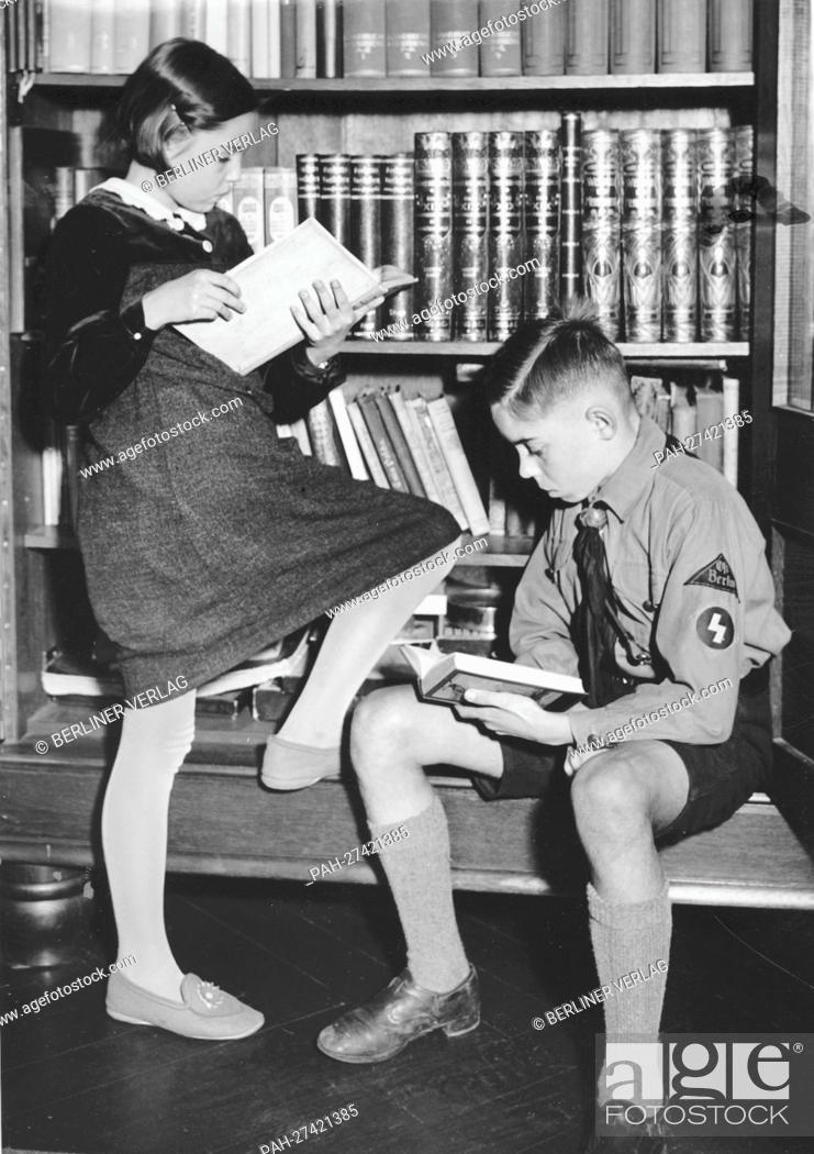 Stock Photo: A boy in the uniform of the German Youth and a young girl are reading books in front of a book shelf in October 1938. The National Socialist propaganda from 19.