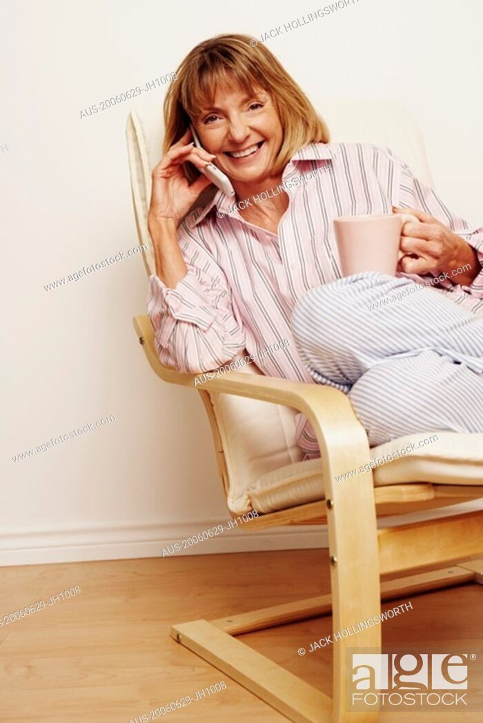 Stock Photo: Portrait of a mature woman holding a cup and talking on a flip phone.