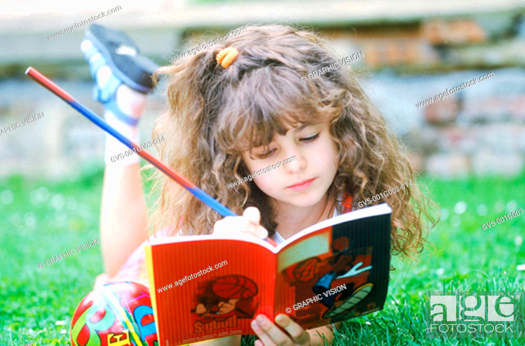 Stock Photo: Young girl lying on lawn writing in book.
