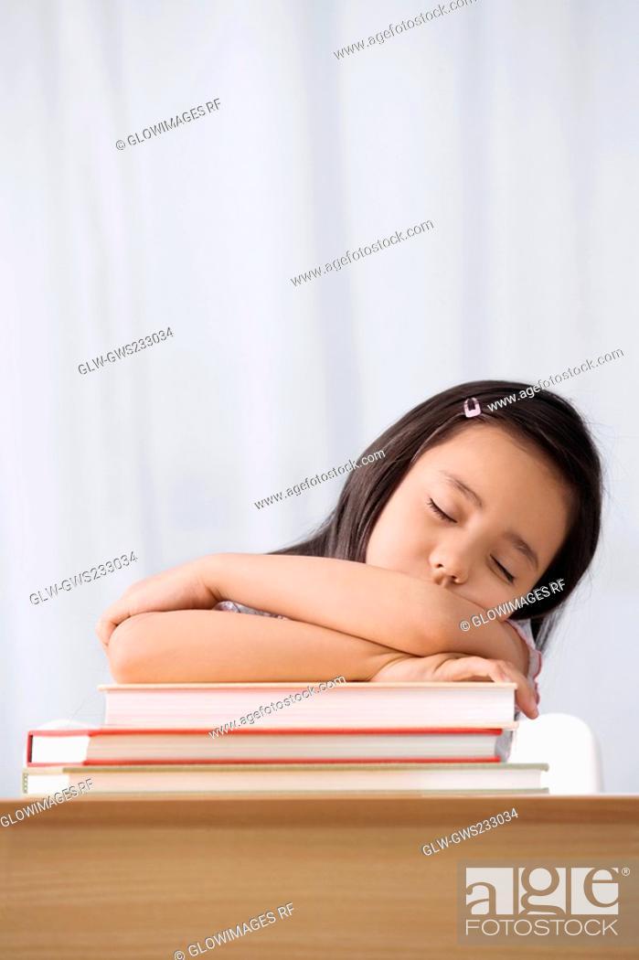Stock Photo: Schoolgirl sleeping at a desk in a classroom.