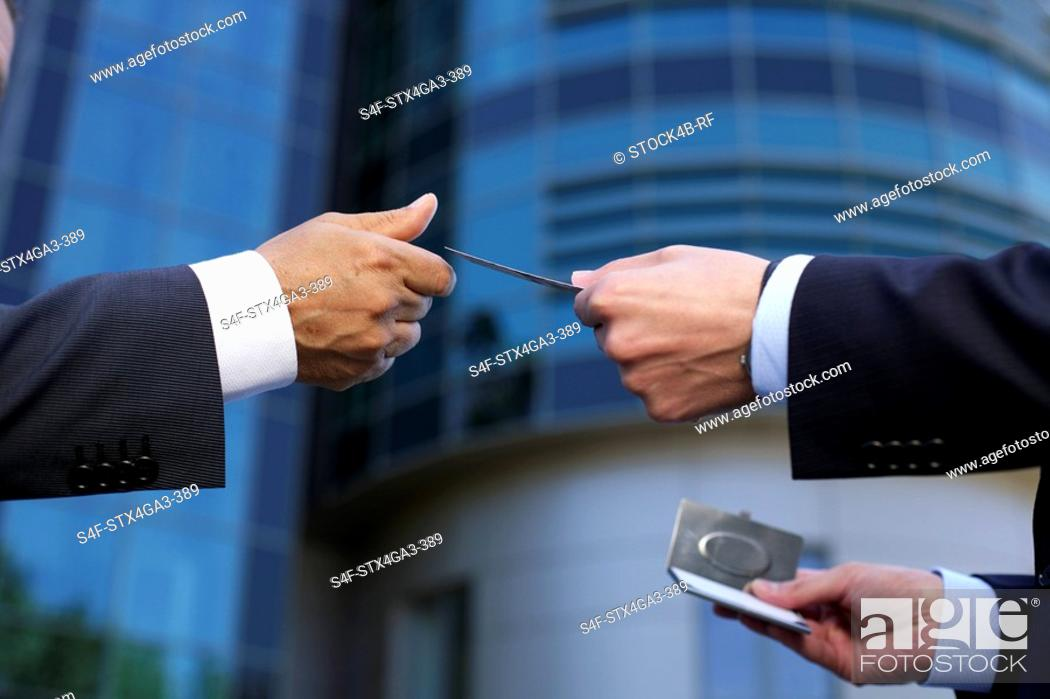 Stock Photo: One hand reaching a business card to another.