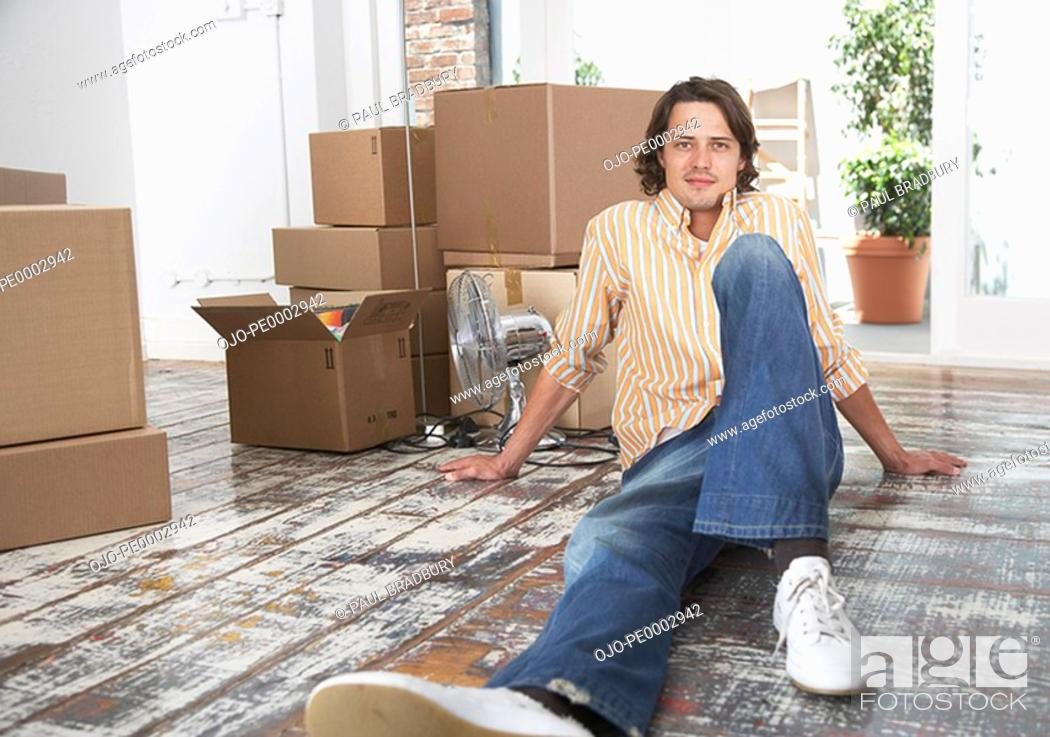 Stock Photo: Man sitting on hardwood floor with cardboard boxes and potted plants smiling.