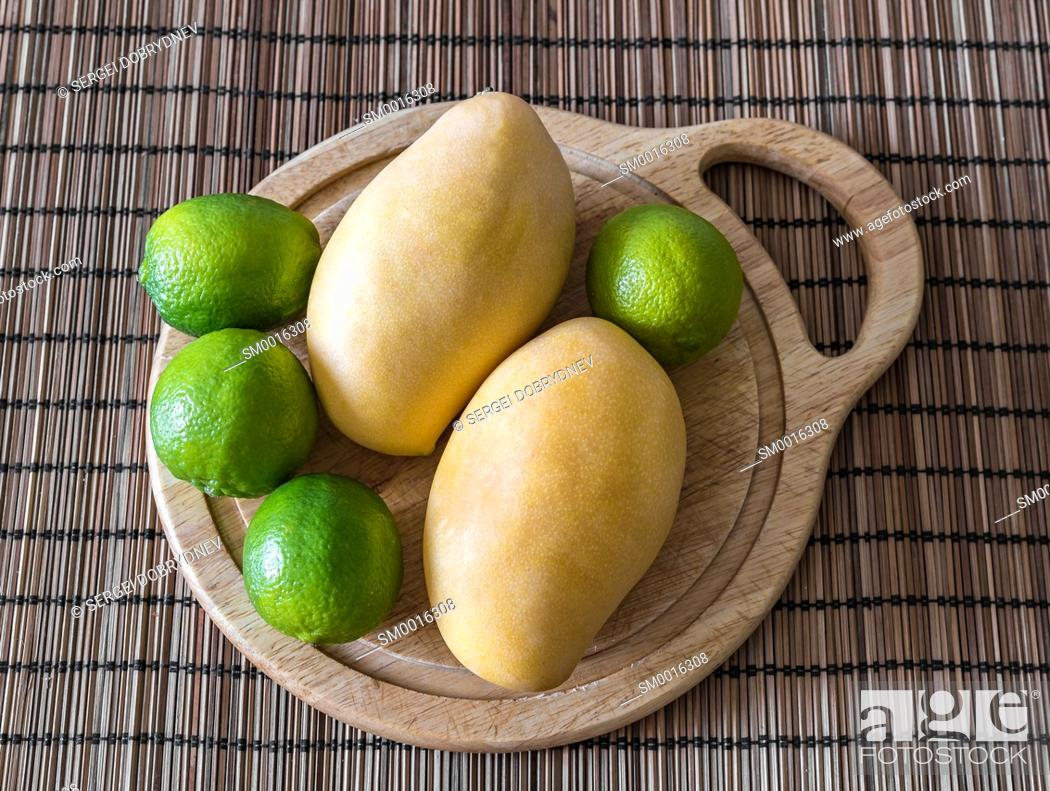 Stock Photo: Mango and lime lie on a cutting board close up.