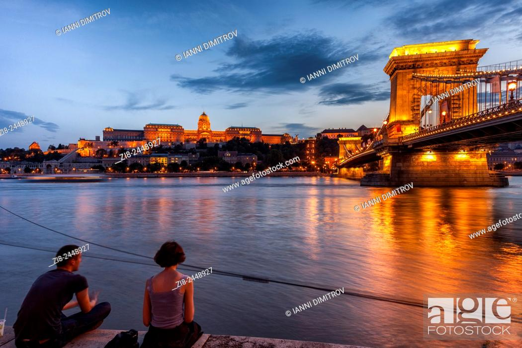 Stock Photo: Young couple on the banks ov river Danube, Buda Castle and Szechenyi Chain Bridge at night, Budapest Hungary.