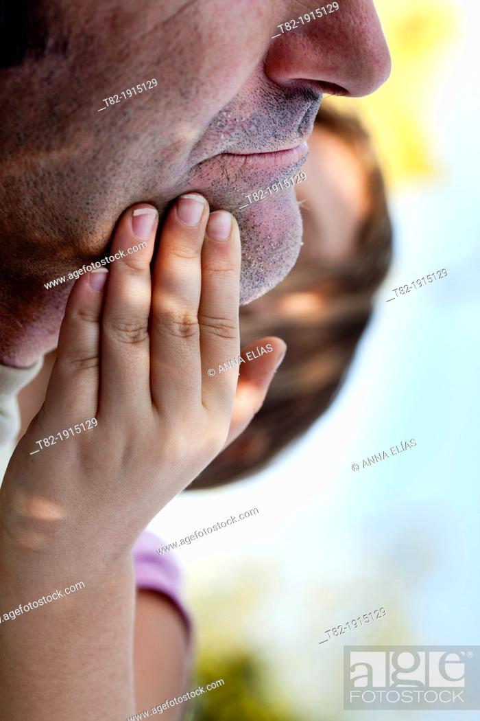 Stock Photo: close-up of hands of 6 year old girl stroking the face of his father.