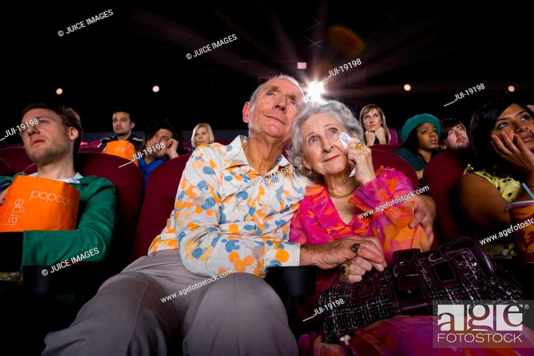 Stock Photo: Senior couple in cinema, man with arms around woman, low angle view.