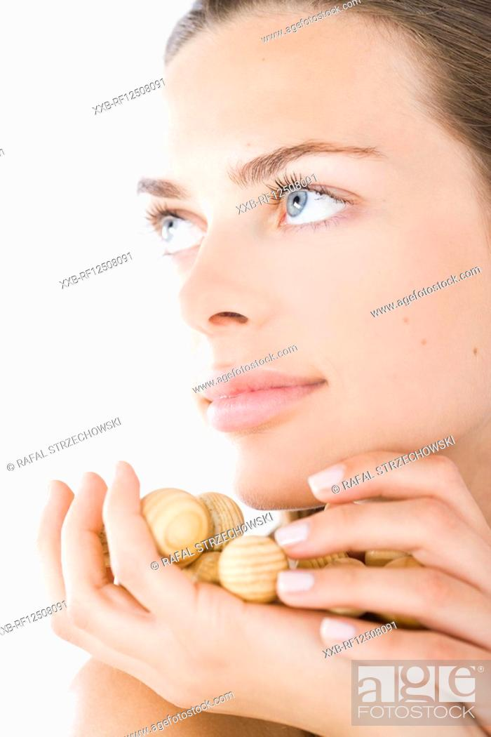 Stock Photo: beauty woman with wodden balls on hand.