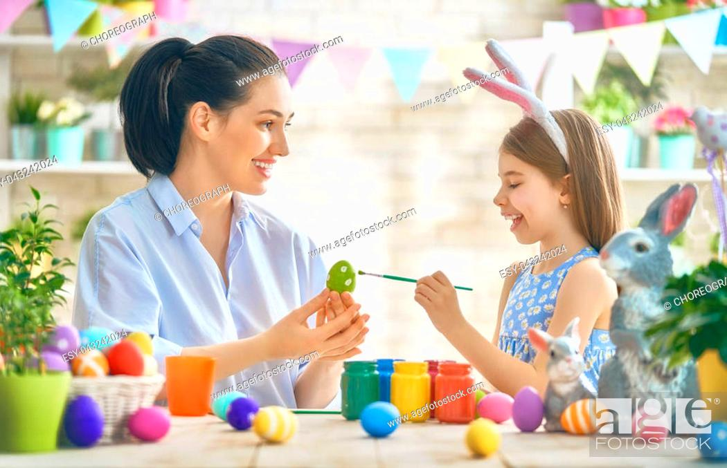 Stock Photo: Happy holiday! A mother and her daughter are painting eggs. Family preparing for Easter. Cute little child girl is wearing bunny ears.