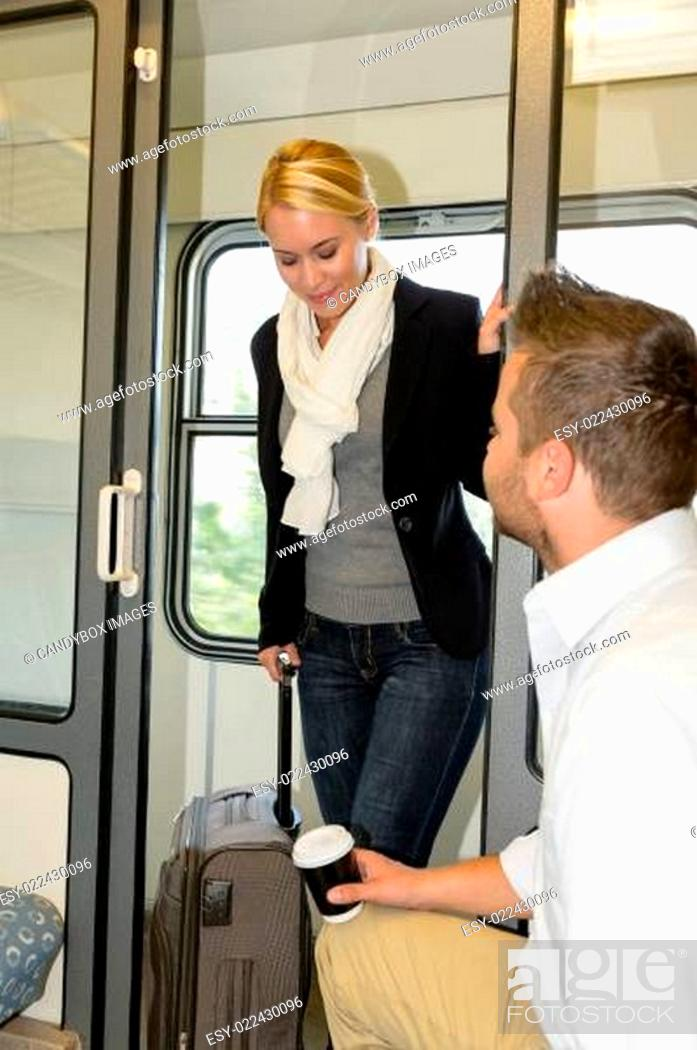 Stock Photo: Man sitting train compartment woman getting in.