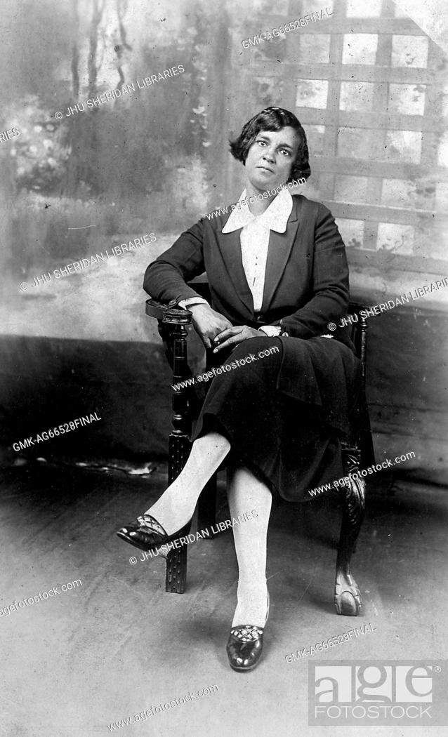 Imagen: Full length sitting portrait, young African American woman, wearing dark dress with light blouse, sitting in front of backdrop, neutral expression, 1920.