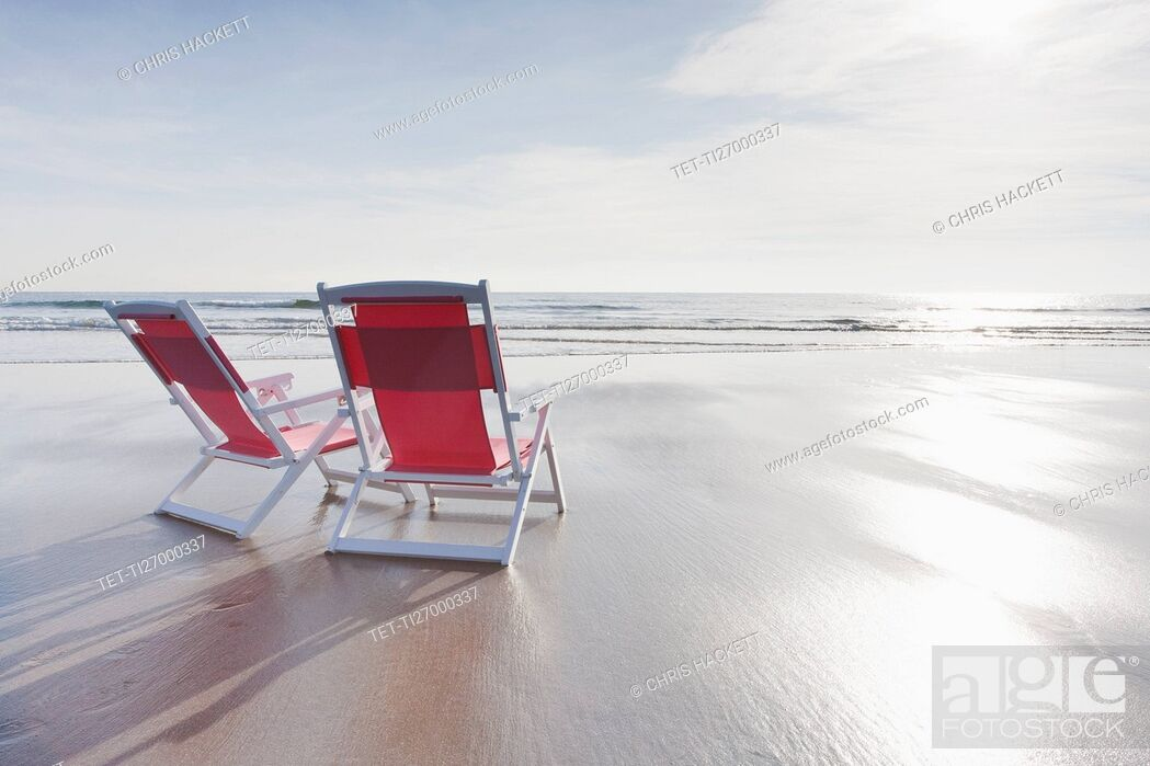 Stock Photo: Maine, Red deckchairs on empty beach.