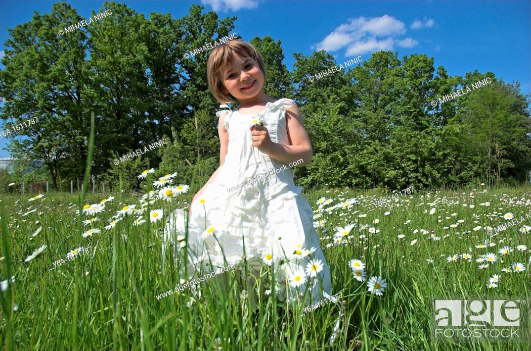 Stock Photo: Little girl wearing white dress standing in field holding daisies smiling portrait.