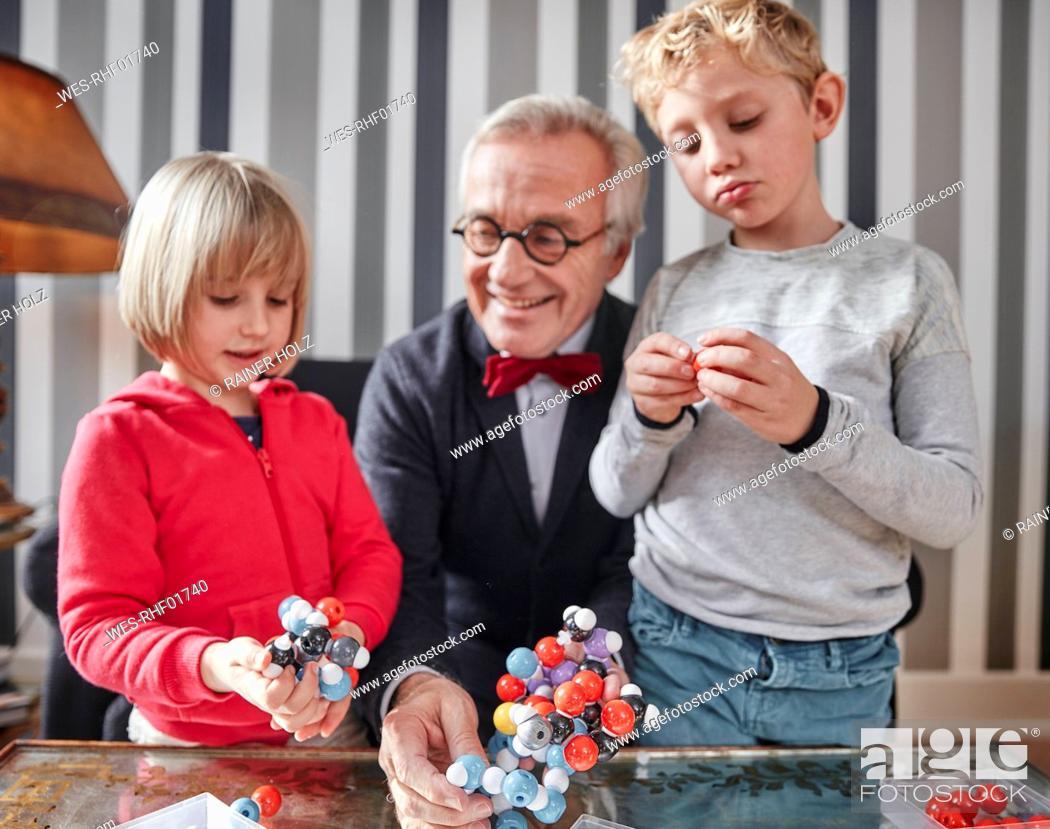 Stock Photo: Grandfather and grandchildren with molecular model.