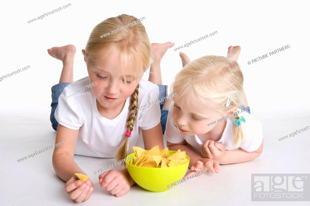 Stock Photo: Two blond girls eating chips.