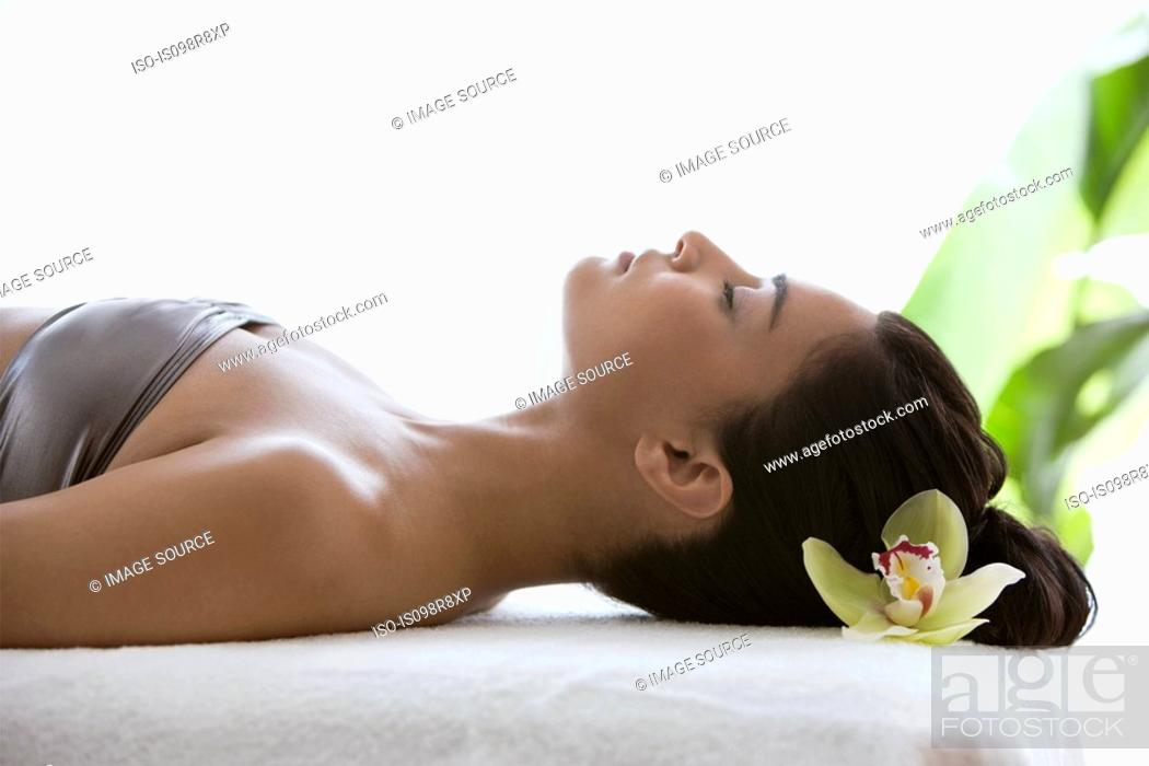 Stock Photo: Young woman on massage table with orchid flower in hair.