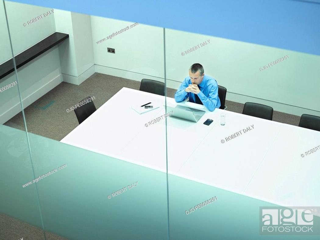Stock Photo: Businessman sitting at table with laptop in office.