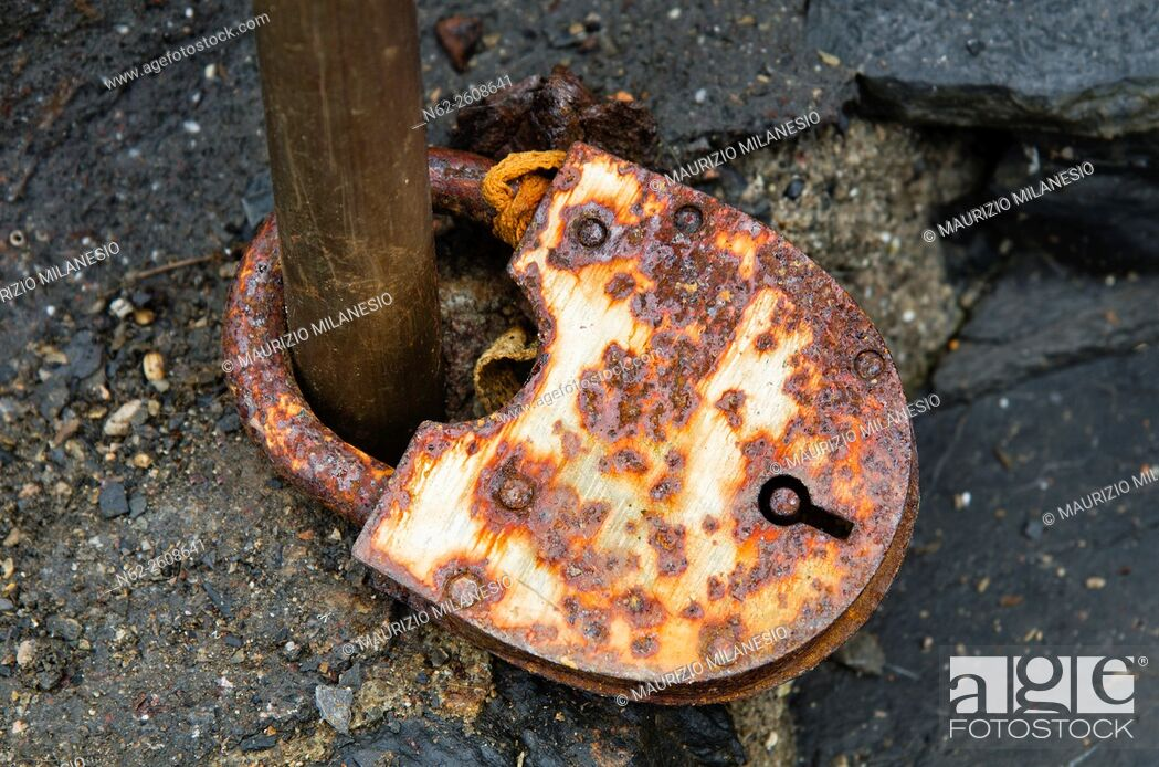 Stock Photo: Old rusty padlock closed to an iron bar.