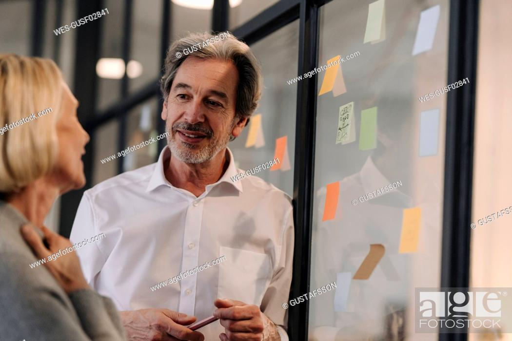 Stock Photo: Businessman and businesswoman working on sticky notes at glass pane in office.