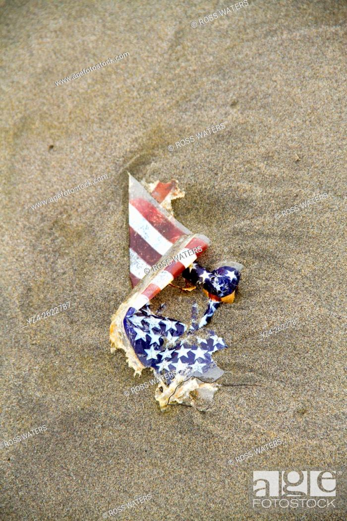 Stock Photo: A damaged American flag on the beach.