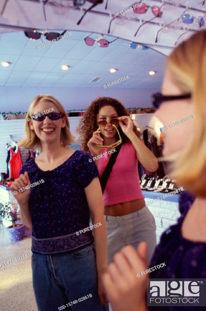 Stock Photo: Three young women shopping for sunglasses.