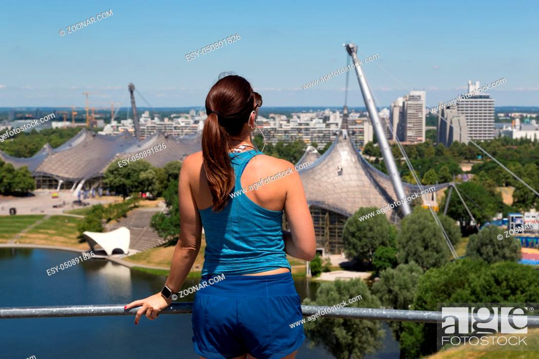 Stock Photo: Female jogger relaxing after working-out listening to music enjoying the view over Munich olympic park.