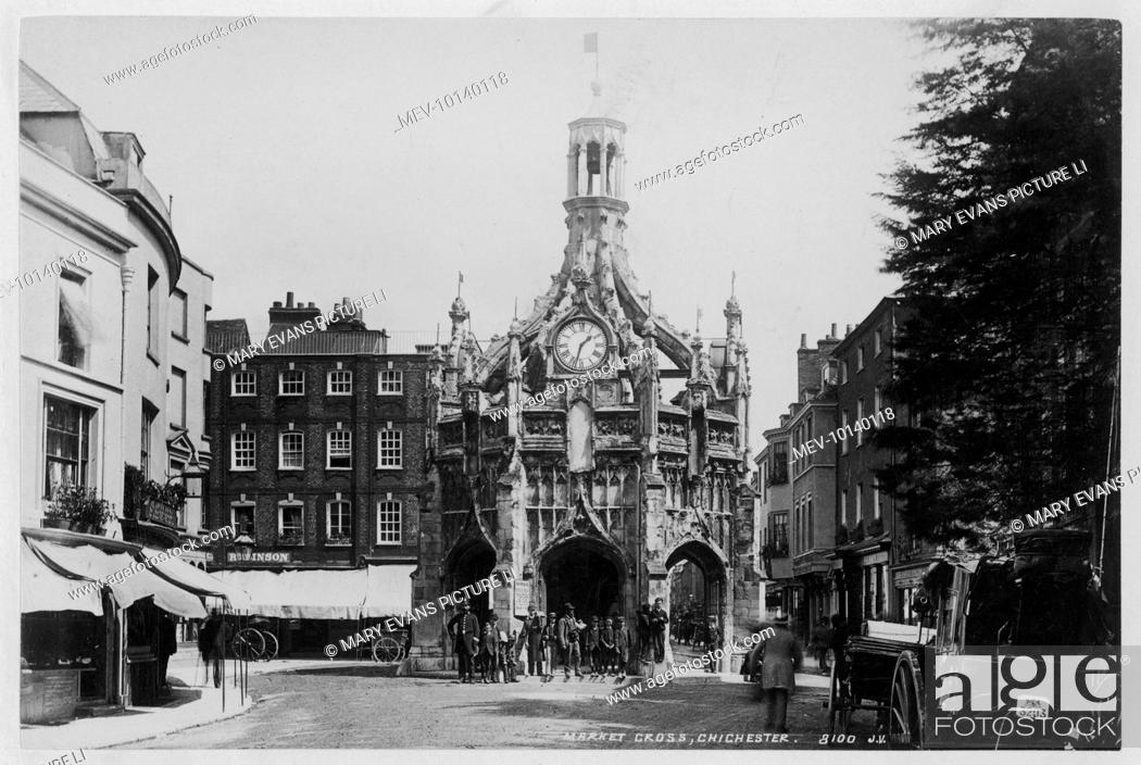 Stock Photo: The Market Cross at Chichester, West Sussex, at 1.30pm : a helpful policeman is holding back pedestrians while the gentleman takes his picture.