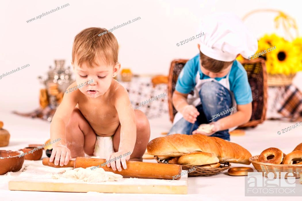 Stock Photo: Cute kids, adorable little girl and funny baby boy wearing chef hats playing with dough baking a pie in a sunny white kitchen.