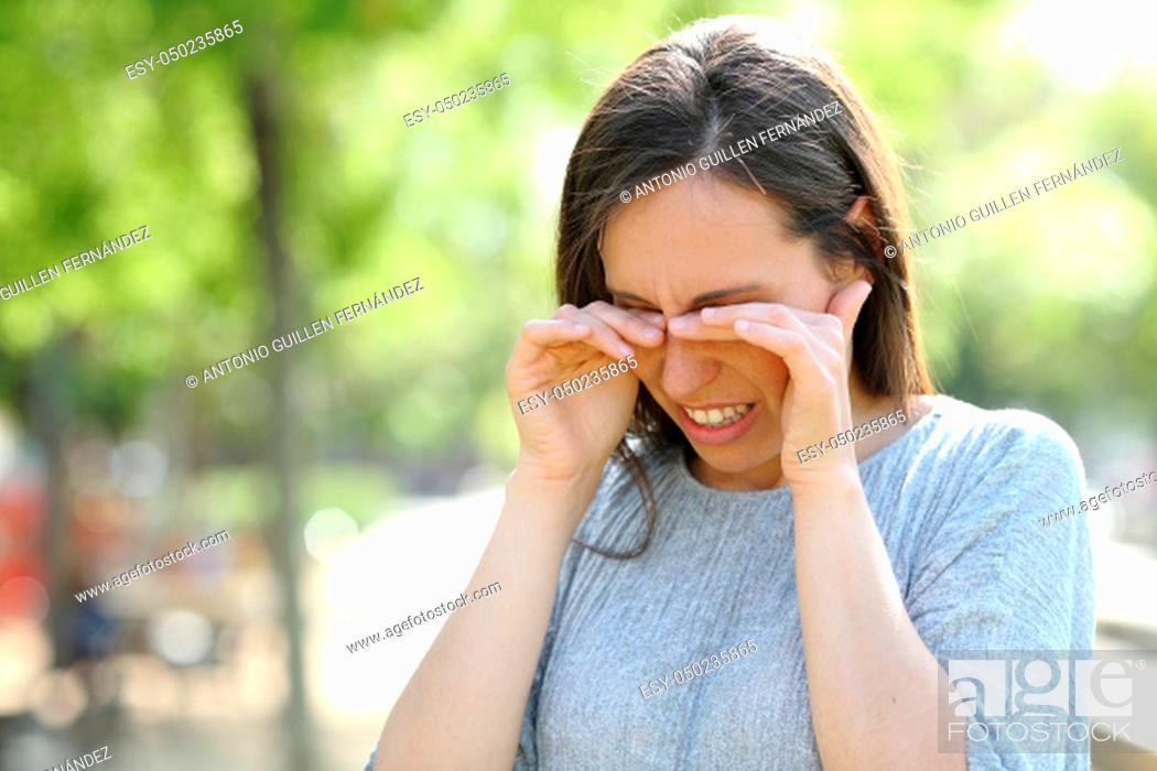 Stock Photo: Disgusted woman rubbing her eyes standing outdoors in a park.