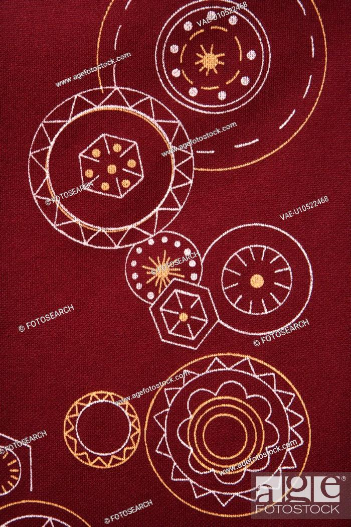 Stock Photo: Close-up of maroon vintage fabric with white and yellow lines and shapes printed on polyester.