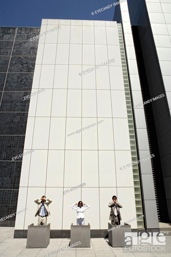 Stock Photo: Three executives are standing outside an office building.