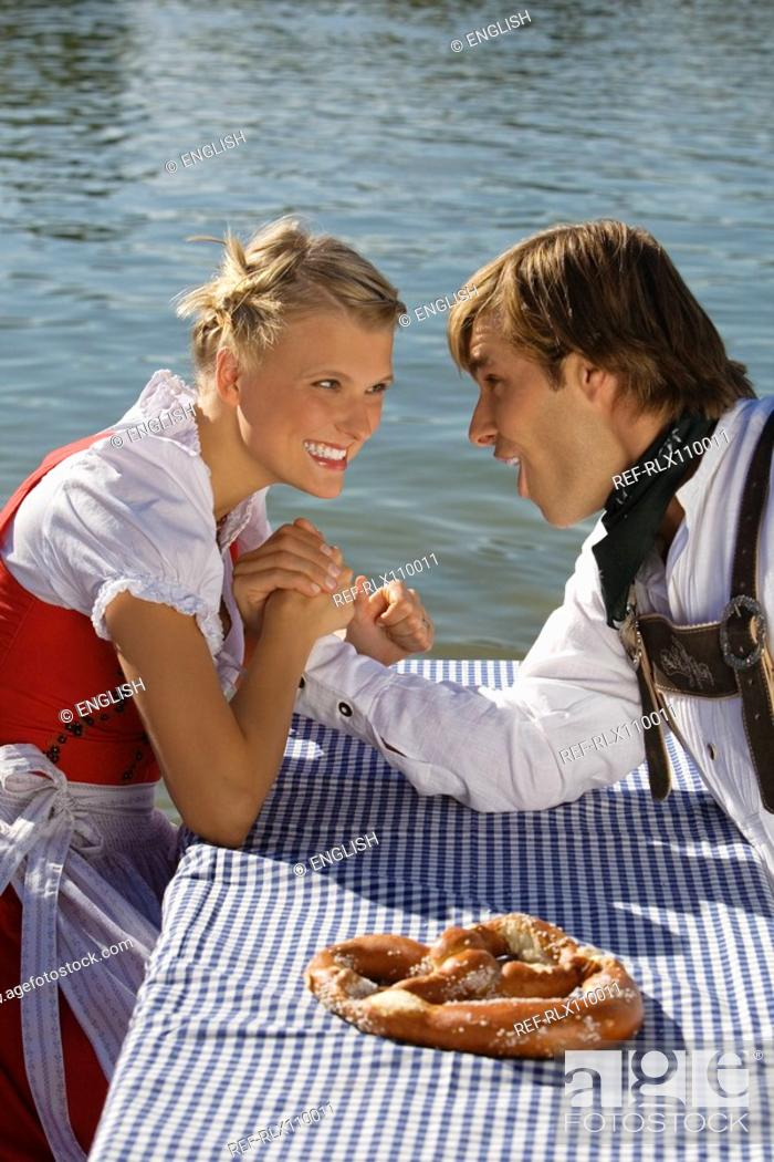 Stock Photo: Young couple in traditional Bavarian outfit, arm-wrestling in Beer garden.