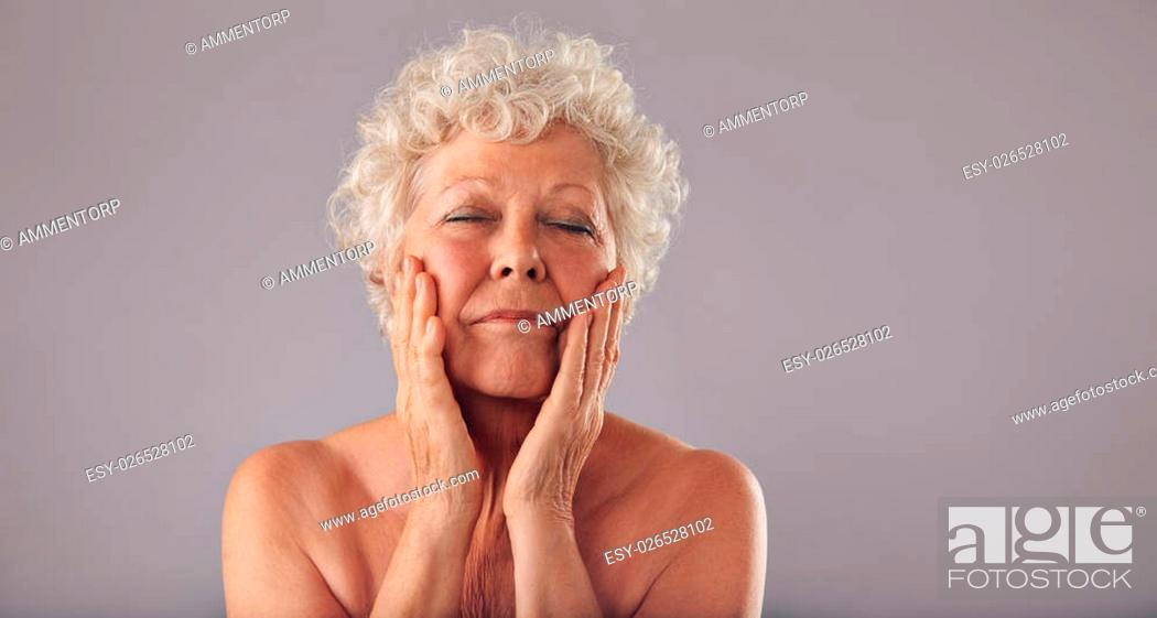 Stock Photo: Portrait of senior woman pampering her face against grey background. Natural woman touching her face.