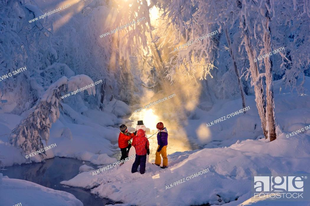 Imagen: Three children building a snowman next to a stream in a frost covered forest, Russian Jack Springs Park, Anchorage, Southcentral Alaska, Winter.