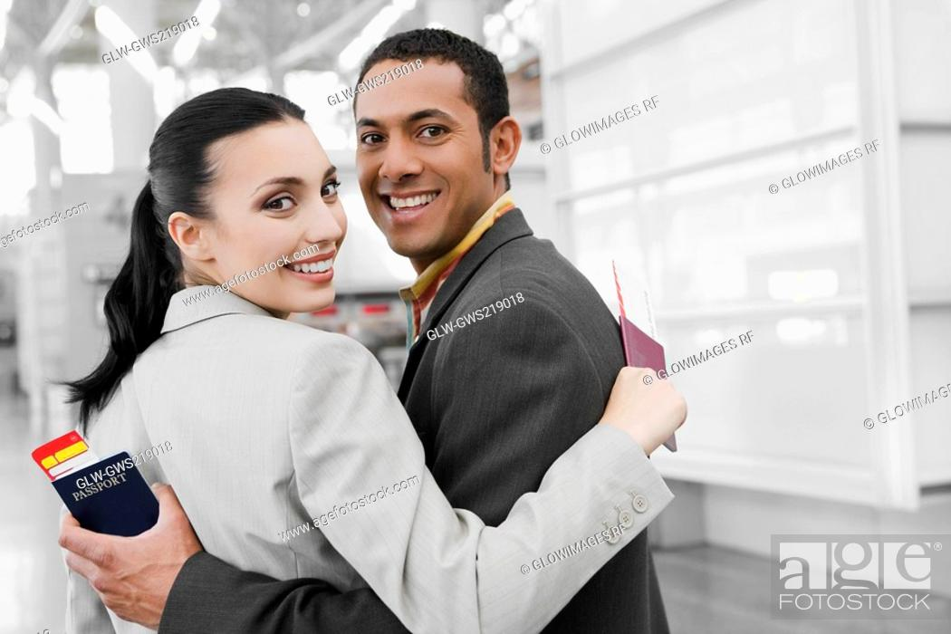 Stock Photo: Portrait of a businessman and a businesswoman with their arms around each other and smiling.