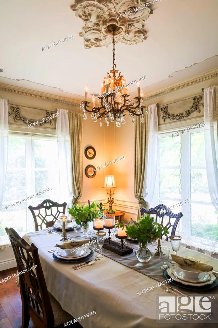 Stock Photo: Set antique wooden dining table with 1850s dishes and hand sculptured sitting chairs in dining room with white lace curtains inside a 2006 reproduction of a.