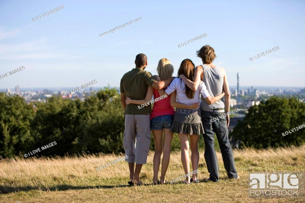 Stock Photo: Four friends in a park looking across the city, rear view.