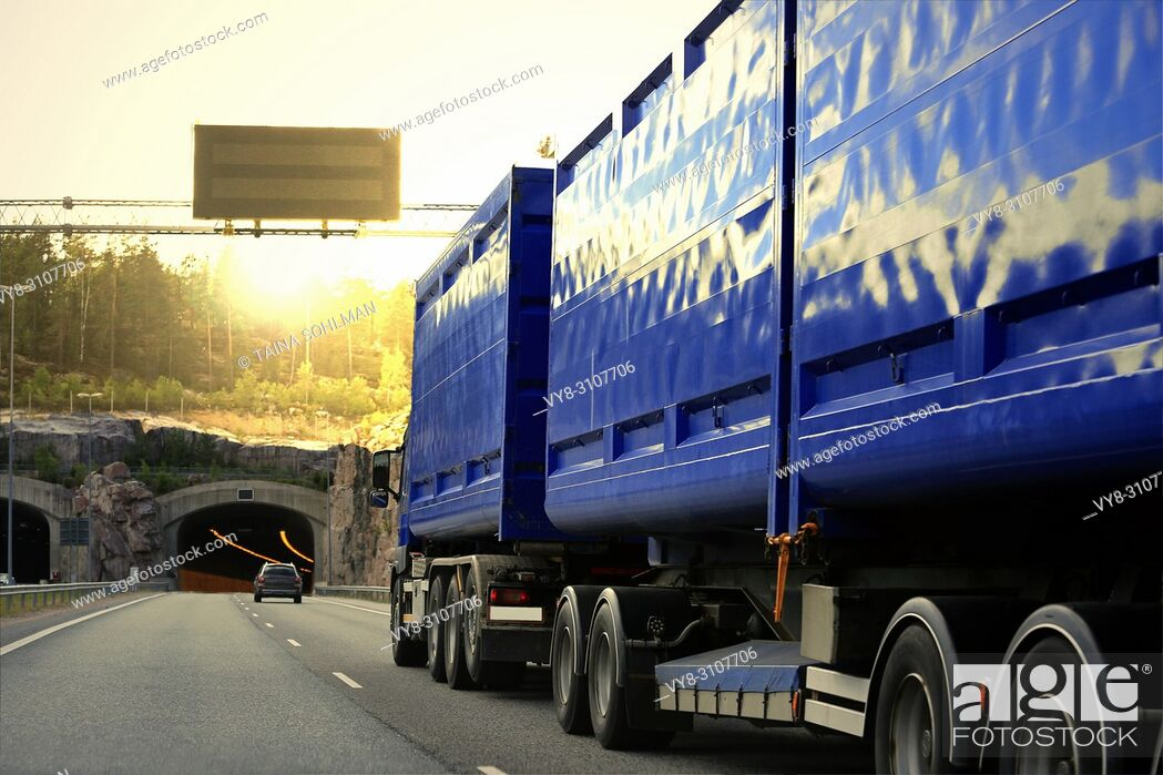 Stock Photo: Blue heavy transport truck drives on motorway among traffic towards a road tunnel and evening sunset.