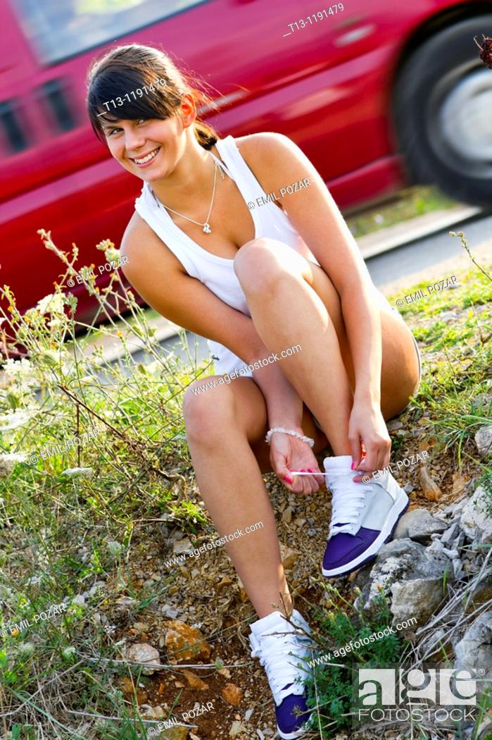 Stock Photo: Tying her sneakers young jogger woman.