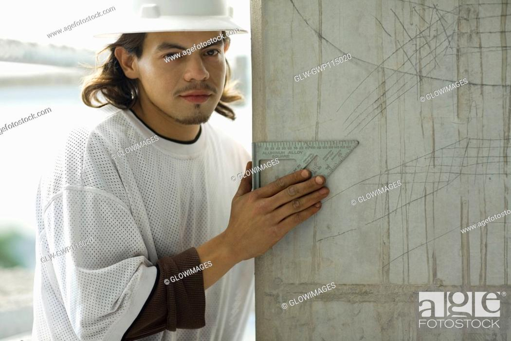 Stock Photo: Portrait of a young man holding a set square.