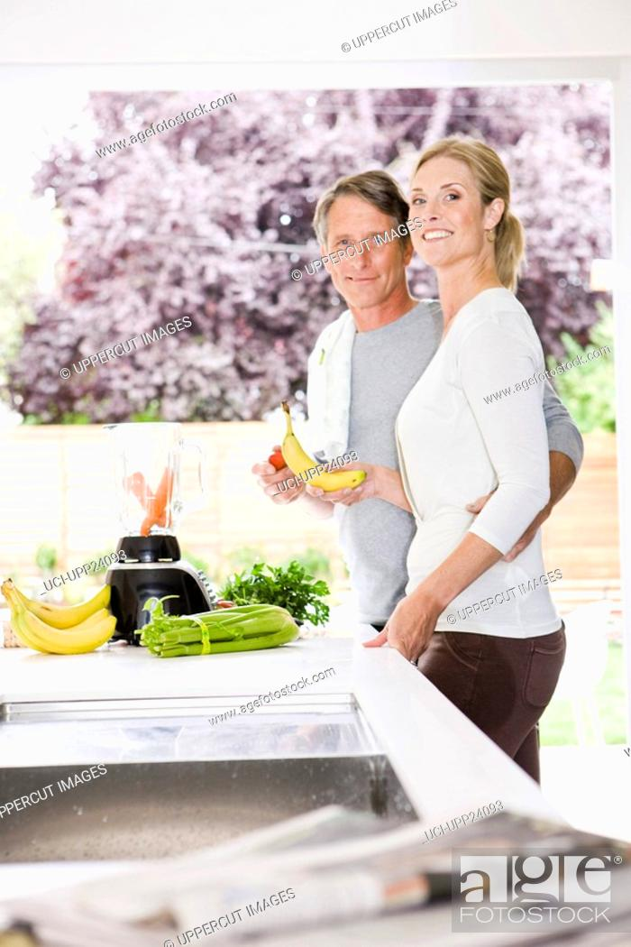 Stock Photo: Portrait of couple preparing health shake in kitchen.