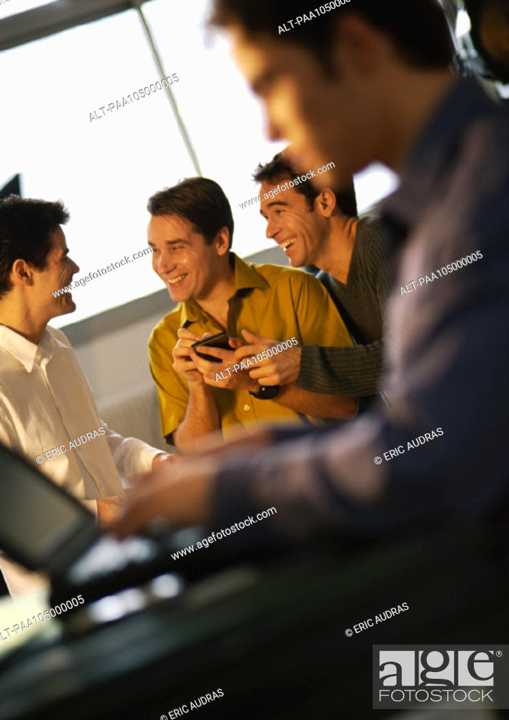 Stock Photo: Three men smiling, one holding a hand held computer, fourth man using laptop in foreground.