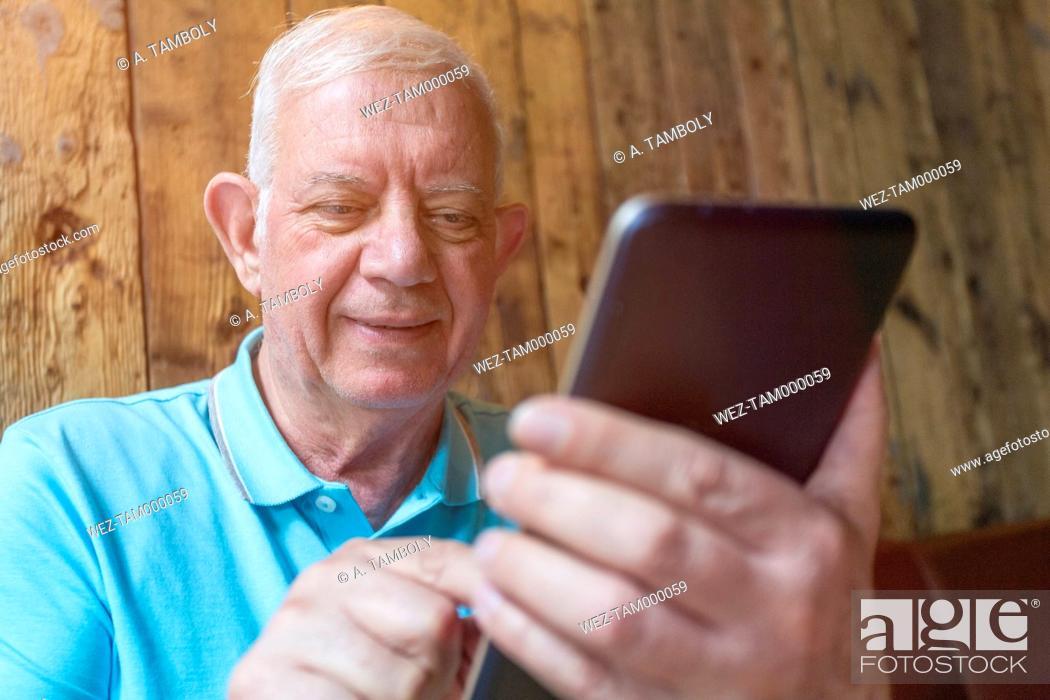 Imagen: Portrait of senior man using phablet.