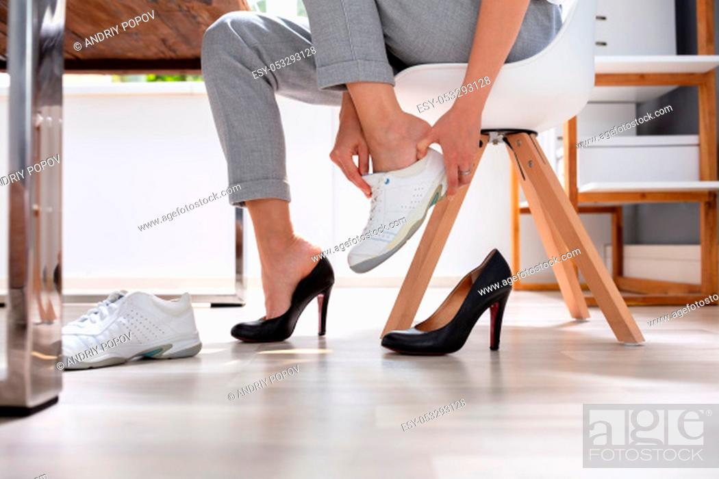 Stock Photo: Close-up Of Businesswoman Removes Black Shoes And Wears Comfortable White Sneakers In Office.