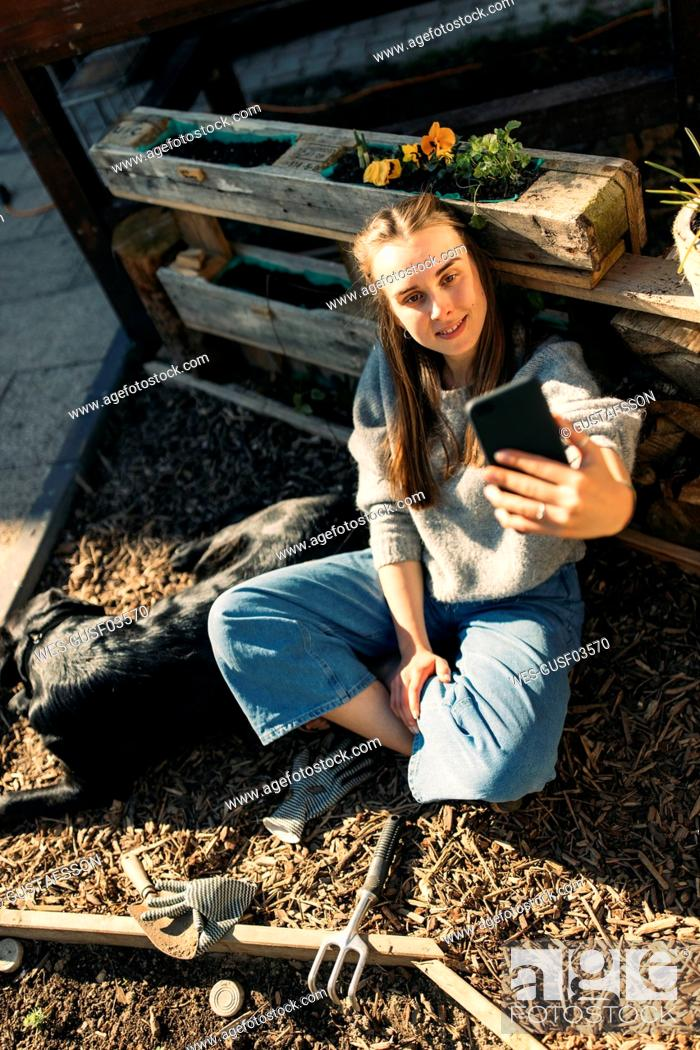 Stock Photo: Happy young woman with dog in garden taking a selfie.